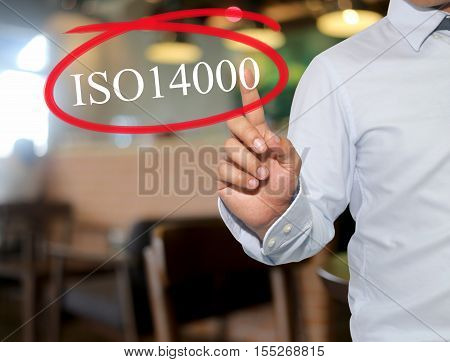 Hand of man touching text ISO14000 with white color on blur interior backgroundconcept of adoption to promote your business for organization.