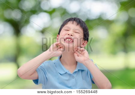 Young asian boy scratching his allergy face outdo