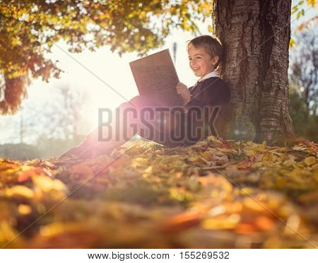 Boy sitting under a tree reading a book in an autumn sunset concept for education and nature