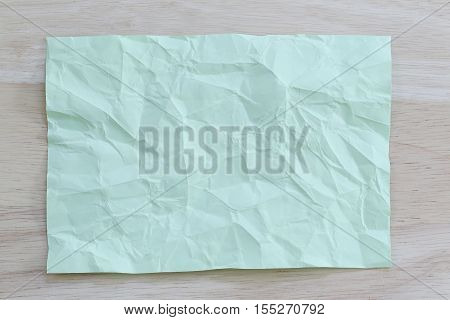 Green notepad paper wrinkled of empty and copy space on wooden backgroundYou can input the message text in picture.
