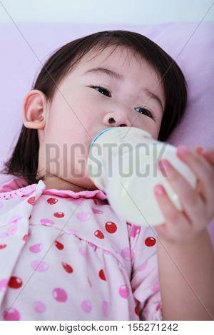 Closeup Cute Asian Girl Suck Up Milk Bottle. Drinking Milk For Good Health.