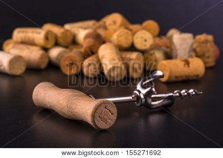 Wine corks and corkscrew on black wooden table