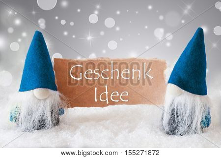 German Text Geschenk Idee Means Gift Idea. Christmas Greeting Card With Two Blue Gnomes. Sparkling Bokeh And Noble Silver Background With Snow.