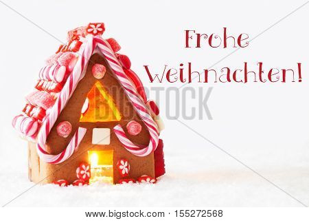 Gingerbread House In Snowy Scenery As Christmas Decoration With White Background. Candlelight For Romantic Atmosphere. German Text Frohe Weihnachten Means Merry Christmas