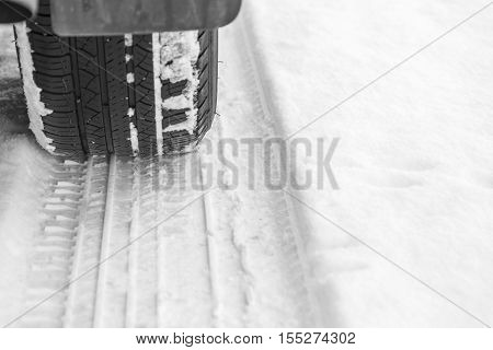 Car tire on snowy road, low angle photograph