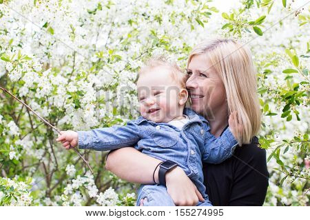 young smiling mother holding her cute cheerful son and enjoying blooming trees in the park at spring
