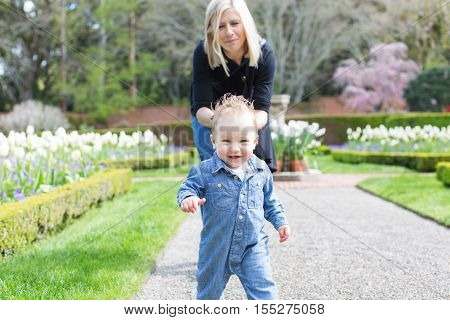 young mother and her toddler son enjoying time together in the park little boy making his first steps