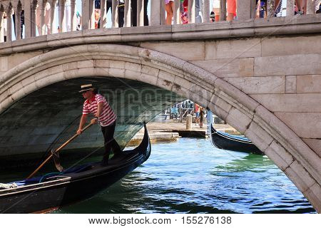 VENICE ITALY - JUNE 06: Venetian gondolier on typical gondola under the bridge in the Venice lagoon on June 06 2016