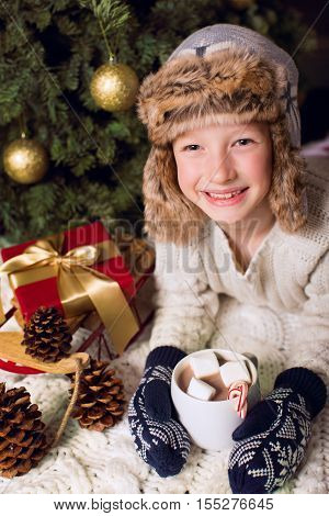 smiling cheerful little boy in cozy hat holding cup with hot chocolate at christmas time by the tree with presents christmas and holiday concept