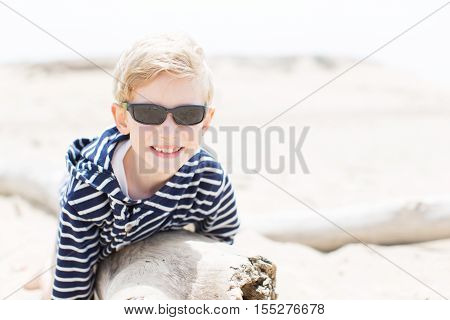 smiling positive boy in sunglasses enjoying warm weather at the beach in california
