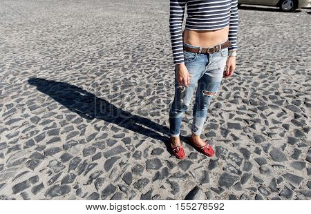 Female foot in torn jeans and red loafers close up copy space