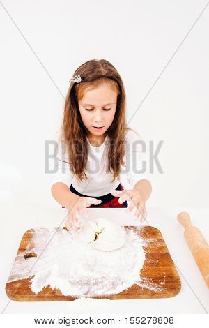 Little girl kneading dough at kitchen. Young lassie cooking bakery for family. Homemade cuisine, children culinary, pastry making concept