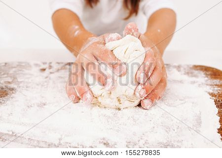 Close-up of kid hands kneading dough. Girl working with raw pastry, bakery cooking.