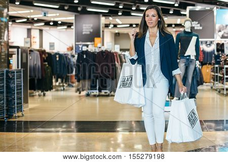 Black Friday. Adult shopping woman takes a walk in a shopping mall. Horizontal indoors shot.