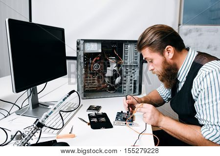 Repairman welding computer circuit in workshop. Bearded engineer fixing electronic component. Repair, development, technology concept