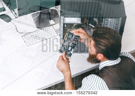 Engineer inspecting microcircuit, double exposure. Electrician examing important component of disassembled computer unit at repair shop