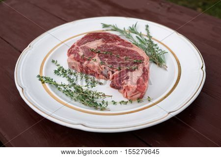 Rib-eye steak in a rustic plate on wooden table