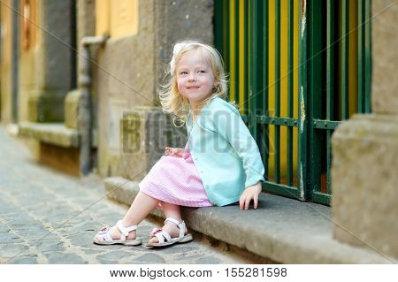 Adorable Little Girl Sitting On A Doorstep On Warm And Sunny Summer Day