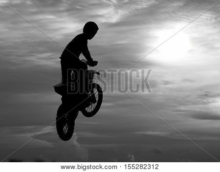 Motocross rider jumping happily. While floating in the sky like birds flying gracefully on a black and white image.
