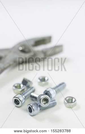 Bolts nuts and a plyer carpenter's tools