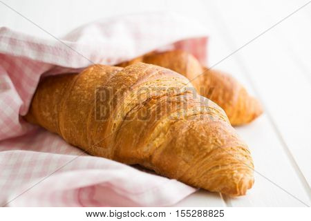 Tasty buttery croissant on white table.