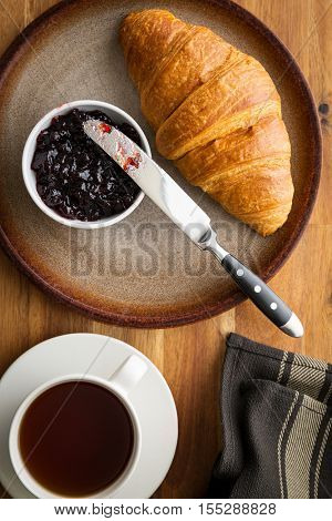 Tasty buttery croissant with jam on plate.