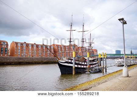 Bremen, Germany - March 23, 2016: A Ship In Front Of Historic Facades Of Houses On Embankment Of Wes