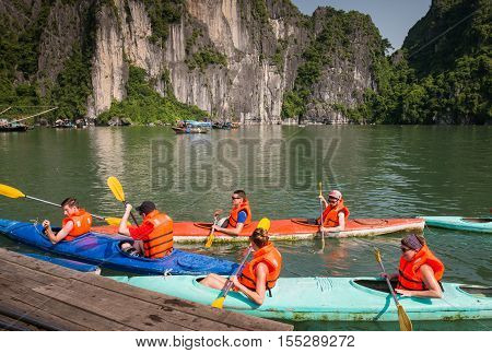 Halong Bay, Vietnam - September 2016: Tourists in kayaks paddling in Halong bay, Vietnam. Rental kayaks in Halong Bay.