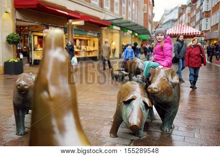 BREMEN GERMANY - MARCH 23 2016: Cute little tourist sitting on popular sculpture of pig family swineherd and his dog in Bremen Germany