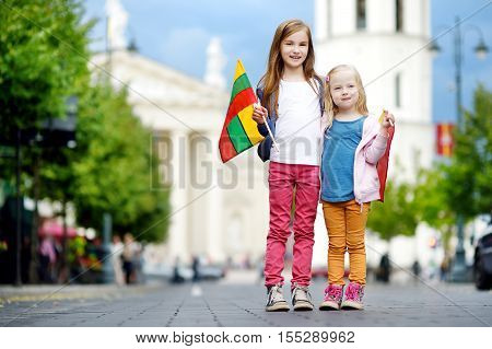 Two Adorable Little Sisters Celebrating Lithuanian Statehood Day Holding Tricolor Lithuanian Flags I