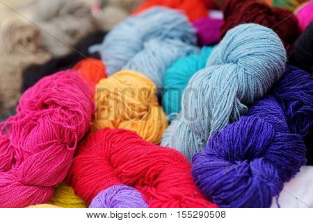 Many colorful skeins of wool felting on a table