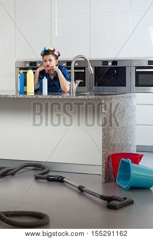Woman With Hair Rollers Sitting Bored In A Beautiful Kitchen