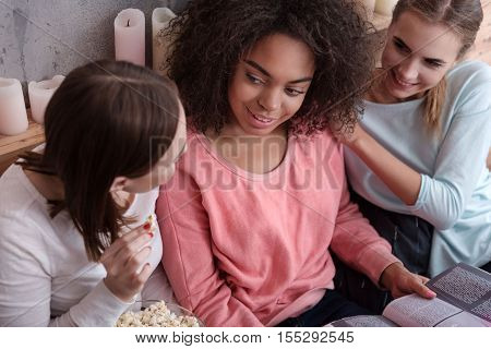 Share opinions. Delighted involved young girls reading the magazine and eating popcorn while lying on the bed at home and sharing opinions