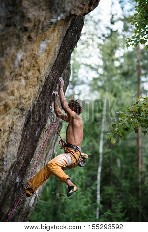Rock climber falling down while ascending an overhanging. Extreme sport climbing.