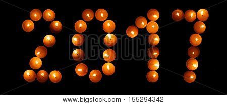 Happy New Year 2017 - festive candles. Happy New Year - 2017 made with candles on black background. Happy new year 2017 - candles. Happy new year 2017 written with burning candles