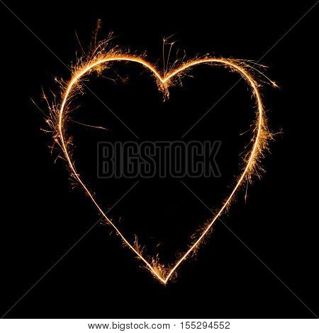 heart from sparkler on black background. Heart from bengal fire. Heart symbol painted with sparkler light. Light painting with fire heart. Love light.Valentine's Day