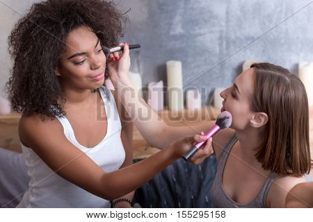 May I help you. Positive smiling involved girls putting the makeup on each other and sitting on the bed while getting ready for a party