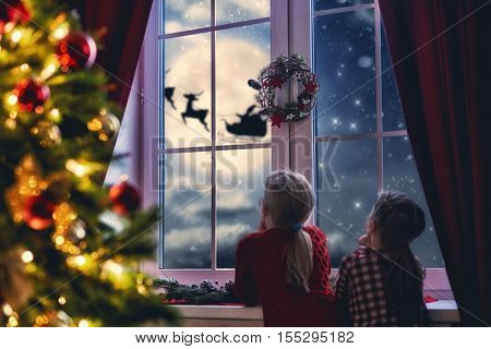 Merry Christmas and happy holidays! Cute little children girls sitting by window and looking at Santa Claus flying in his sleigh against moon sky. Room decorated on Christmas. Kids enjoy the holiday.