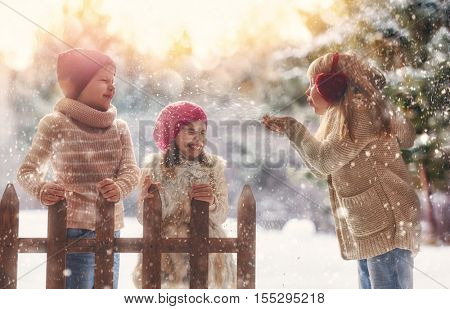 Cute children girls and boy playing on a winter walk in nature. Happy kids outdoors.