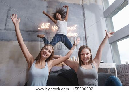 Joyful home party. Amused joyful young girl jumping on the bed in the bedroom while expressing joy with friends and raising their hands