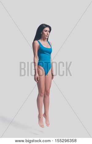 Beauty in mid-air. Full length of attractive young woman in blue swimsuit jumping in front of grey background