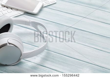 Headphones, smartphone and pc keyboard on wooden desk table. Music concept. View with copy space