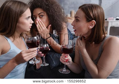 A new gossip. Pleasant delighted young girls gossiping and sitting in the bedroom while expressing interest and drinking wine