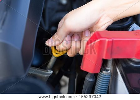Asian woman's hand checking level of lubricant oil of car engine. poster