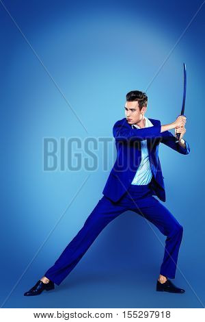 Businessman in a fighting stance with a sword in his hands. Struggle and competition concept.
