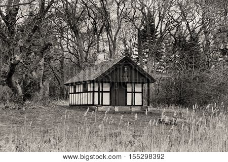Black and white shot of a hunting hut in a forest
