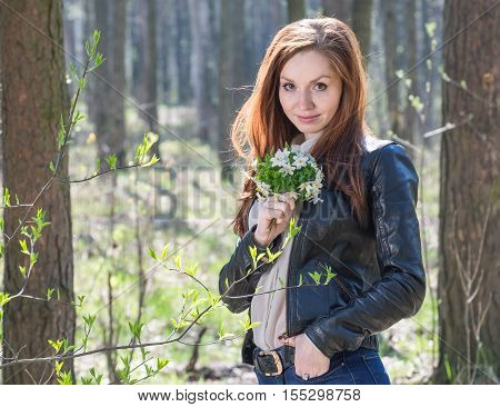 Young lovely redhead girl with bouquet of spring flowers while walking at park