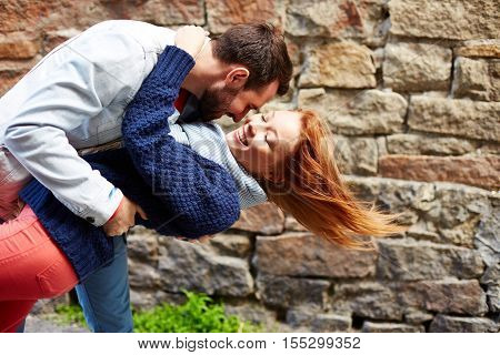 Man holding his girlfriend falling backwards like in a dance move