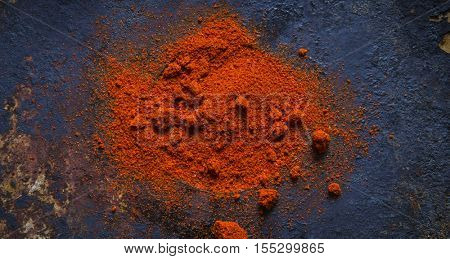 Paprika powder on a black background.