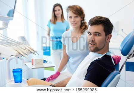 Young male patient sitting in dentist's chair, female dentist sitting by him.